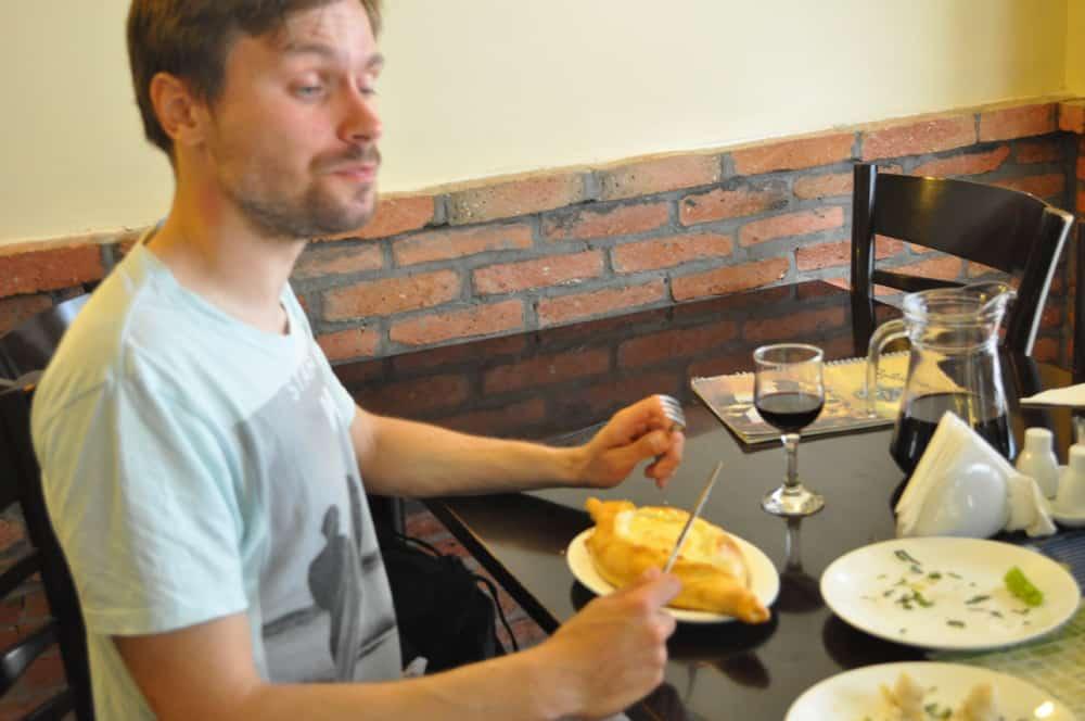 Adrian pokazuje jak jeść adżarskie chaczapuri. Nożem i widelcem.